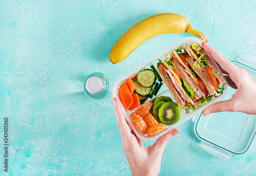 In de dag Assortiment Lunchbox in hands. School lunch box with sandwich, vegetables, water, and fruits on table. Healthy eating habits concept. Flat lay. Top view