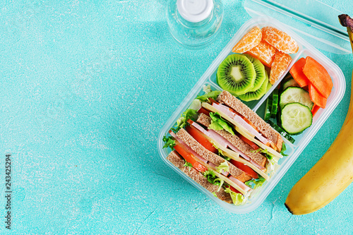 Fotografía School lunch box with sandwich, vegetables, water, and fruits on table