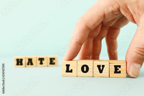 Man Hand Picking Wooden Cubes With The Text LOVE Over HATE