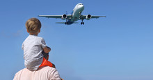 Father And Son Watching The Landing Planes. Traveling On An Airplane With Children