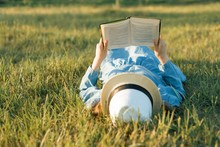 Girl In Dress And Hat Lies On Green Grass Reading Book. View From Above