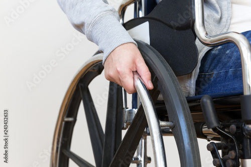 Fotografiet  Detail of disabled woman holding a hand on wheel of a wheelchair.