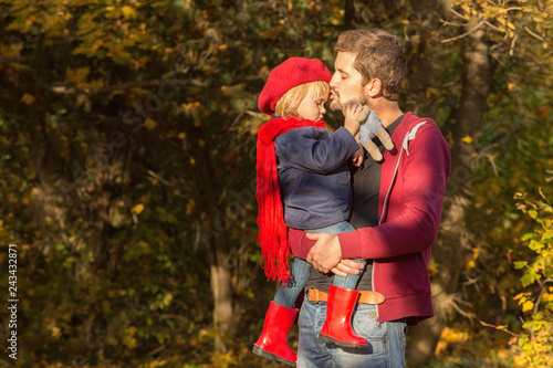 Fotografering  Dad is kissing the forehead of his tiny daughter in an autumn park at sunset