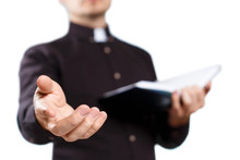 Young Priest Reading The Holy Bible And Stretching His Hand, Isolated On White Background