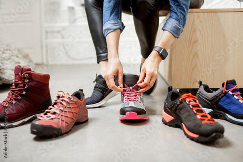 Cuadros en Lienzo Woman trying different trail shoes for mountain hiking in the sports shop, close