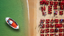 Aerial Drone Top View Photo Of Iconic Beach Of Psarou With Emerald Clear Sandy Organised Beach With Sunbeds And Umbrellas And Traditional Fishing Boat, Mykonos Island, Cyclades, Greece