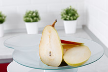 Ripe Pear Slices In A Juicer And A Glass Of Fresh Juice In The Kitchen.