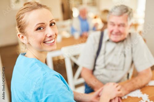 Fotografia  Lächelnde Pflegehilfe tröstet einen Senior