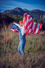 Boy In Nature Holding An American Flag