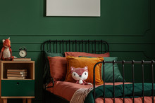 Plush Toy, Clock And Books On Bedside Table Next To Single Metal Bed With Cozy Bedding And Plush Fox