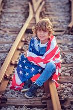 Boy Sitting On Train Tracks Holding An American Flag