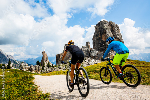 Garden Poster Cycling Couple cycling in Cortina d'Ampezzo, stunning Cinque Torri and Tofana in background. Woman and man riding MTB trail. South Tyrol province of Italy, Dolomites.