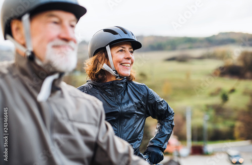 Obraz Active senior couple with electrobikes standing outdoors on a road in nature. - fototapety do salonu