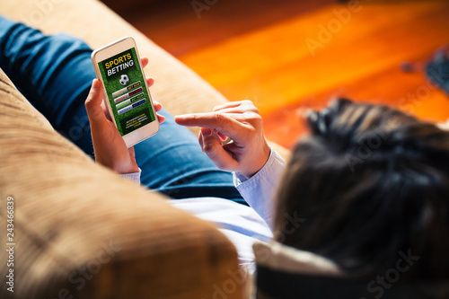 Photo Woman holding a mobile phone to visit a sports betting website while lies down at home