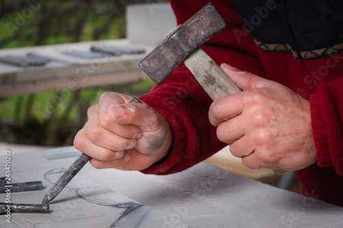 Craftsman hands, working the stone with his tools and blurred background