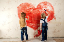 Childrens  Painted The Wallpaper In The Room With Red Paint. Paint The Walls With A Roller. The Girl  And Boy Painted A Heart On The Wall. Valentine's Day, A Gift To Parents.