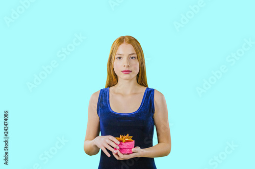 Photo  Cute beautiful girl with long red hair holding a box with a gift and looking into the camera on an isolated background, gifts for the New Year holidays