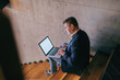 Middle-aged businessman dressed smart casual sitting on the stairs indoors and using laptop for work.