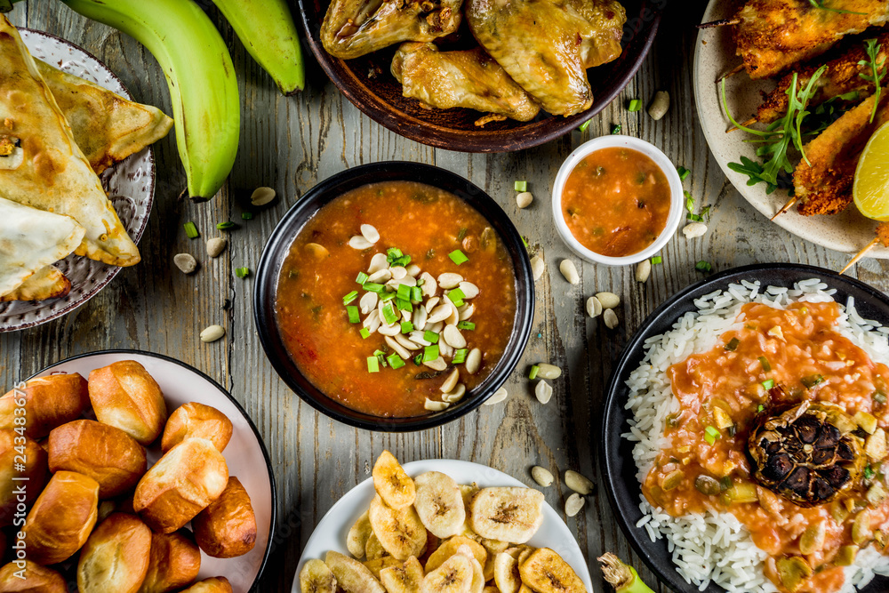 Fototapety, obrazy: West african food concept. Traditional Wset African dishes assortment - peanut soup, jollof rice, grilled chicken wings, dry fried bananas plantains, nigerian chicken kebabs, meat pies, top view