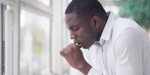 Fototapeta Sick African man coughing; Portrait of ill black man cough due to cold, flu, all