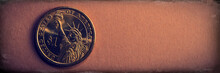 One Dollar Coin Lies On A Brown Paper Background. Web Banner.