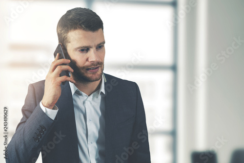 business communication - young businessman talking on the phone in office