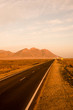 long straight road in the desert and a mountain at the end