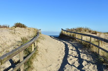 Beach With Big Sand Dunes With Vegetation And Wooden Fence. Sunny Day, Morning Light, Galicia, Coruna, Spain.