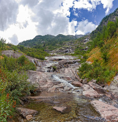 Fototapeta na wymiar Panoramic view of a stream flowing on the steep rocky walls of Monte Rosa in Piedmont, Italy.