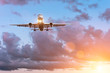 Plane on the glide path before landing on the background of a beautiful sunset and picturesque clouds.