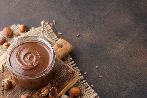 Valokuvatapetti Chocolate spread with hazelnuts on brown countertop