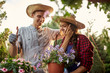 Happy guy and girl gardeners in a straw hats hold pots with petunia on the garden path in on a sunny day.