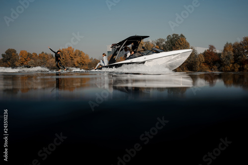Girl riding on the wakeboard on the high wave of the motorboat