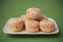Closeup Of Mini Doughnuts In A White Plate  On Green Background