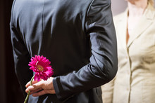 A Young Man In A Suit Holds A Gerbera Flower Behind His Back, A Surprise For A Woman, March 8