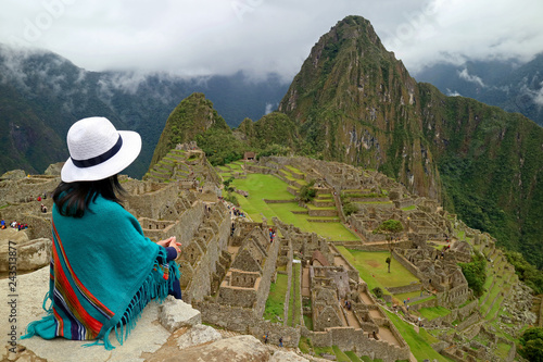 Photo  Female Traveler Sitting on the Cliff Looking at the Inca ruins of Machu Picchu,