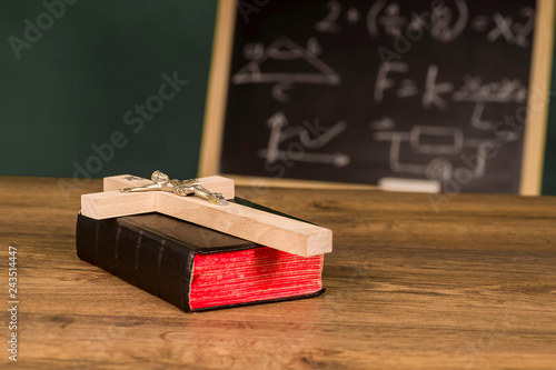 Fotografie, Obraz  A crucifix on a book against the background of a chalkboard