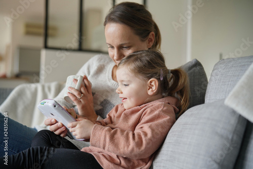 Fototapeta Mother and young daughter playing games on child's tablet at home obraz na płótnie