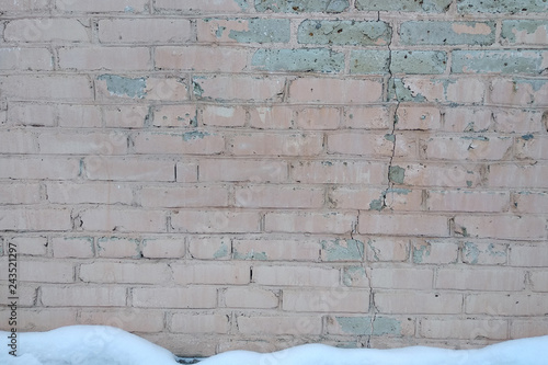Fotografía  Snow covered old wall of red brick.