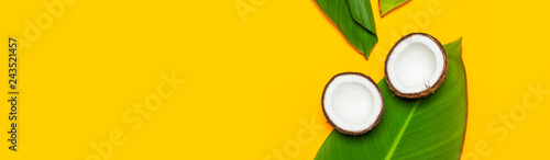 Obraz na plátně Ripe coconut and tropical leaves on yellow colored background, minimal flat lay style top view
