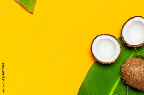 Ripe coconut and tropical leaves on yellow colored background, minimal flat lay style top view. Pop art design, creative summer and food concept. Tropical fruit whole and half abstract background