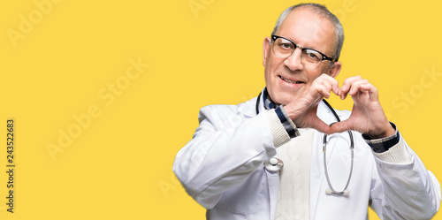 Fotografía Handsome senior doctor man wearing medical coat smiling in love showing heart symbol and shape with hands