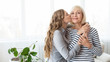 canvas print picture - Young daughter kissing senior mother on the cheek