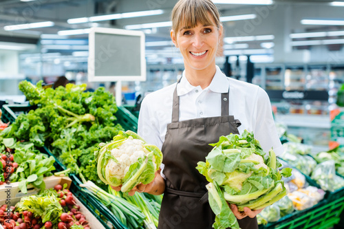 Slika na platnu Shop assistant woman in supermarket showing the fresh produce with pride looking