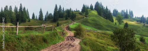 amazing mountain view. wooden fence and high mountain village. summer landscape. beautiful natural background