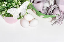 Easter White Chicken Eggs And Green Spring Plant In Flower Pot, Decorative Butterfly And A Basket With Woolen Scarf On White Table With Copy Space