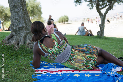 Photo  African girl in a bright outfit lying on the grass in the shade of a tree