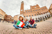 17 OCTOBER 2018, SIENA, ITALY: Travel With Group Of Friends In Italy. Multiethnic Diverse Group Of Young People Having Fun In Front Of A Famous Landmark The Tower In Siena, Tuscany