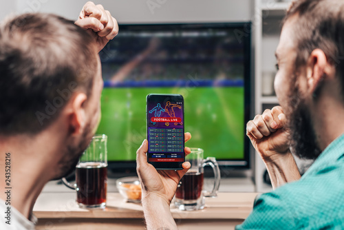Two male friends watching live football game broadcast on tv Fototapete