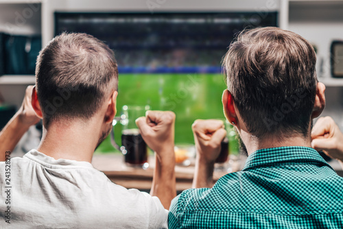 Foto Two male friends watching live football game broadcast on tv